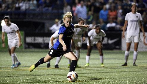 Seattle Reign FC's Kim Little (8) shoots a penalty kick against the Washington Spirit to tie the game in the second half of a NWSL semifinal soccer match Sunday, Aug. 24, 2014, in Seattle. The Reign won 2-1