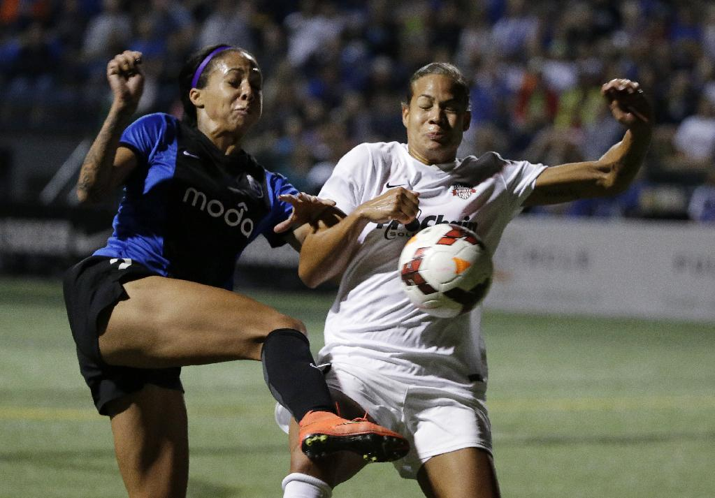 Seattle Reign FC's Sydney Leroux, left, and Washington Spirit's Toni Pressley collide in front of the Washington goal in the second half of a NWSL semifinal soccer match Sunday, Aug. 24, 2014, in Seattle. Washington was called for a foul on the play and Seattle scored on a penalty kick. The Reign won 2-1