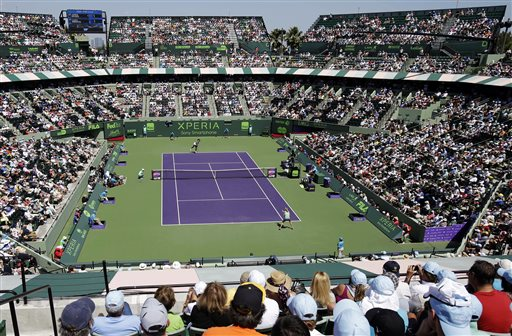 Fans watch as Serena Williams, rear, serves to Maria Sharapova, of Russia, during the final match of the Sony Open tennis tournament, Saturday, March 30, 2013, in Key Biscayne, Fla