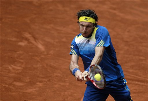 Juan Monaco from Argentina returns the ball to Janko Tipsarevic from Serbia during the Madrid Open tennis tournament, in Madrid, Tuesday, May 7, 2013