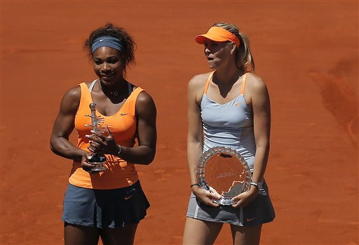 Serena Williams from the U.S., left, poses for photographers alongside Maria Sharapova from Russia after her victory in the women's final match at the Madrid Open tennis tournament, in Madrid, Sunday, May 12, 2013