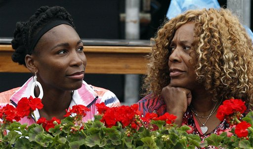 Venus Williams, of the United States, left, flanked by her mother Oracene, looks on during the match between her sister Serena Williams and Slovakia's Dominika Cibulkova, at the Italian Open tennis tournament in Rome, Thursday, May 16, 2013