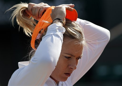 Russia's Maria Sharapova adjusts her cap during a training session for the 2013 French Open tennis tournament, at Roland Garros stadium in Paris, Saturday May, 25, 2013