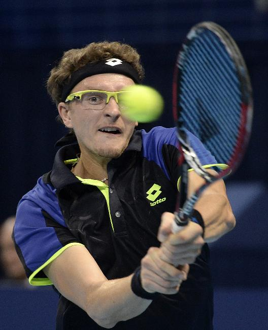 Uzbekistan's Denis Istomin returns a ball to Switzerland's Roger Federer during their second round match at the Swiss Indoors tennis tournament at the St. Jakobshalle in Basel, Switzerland, Wednesday Oct. 23, 2013