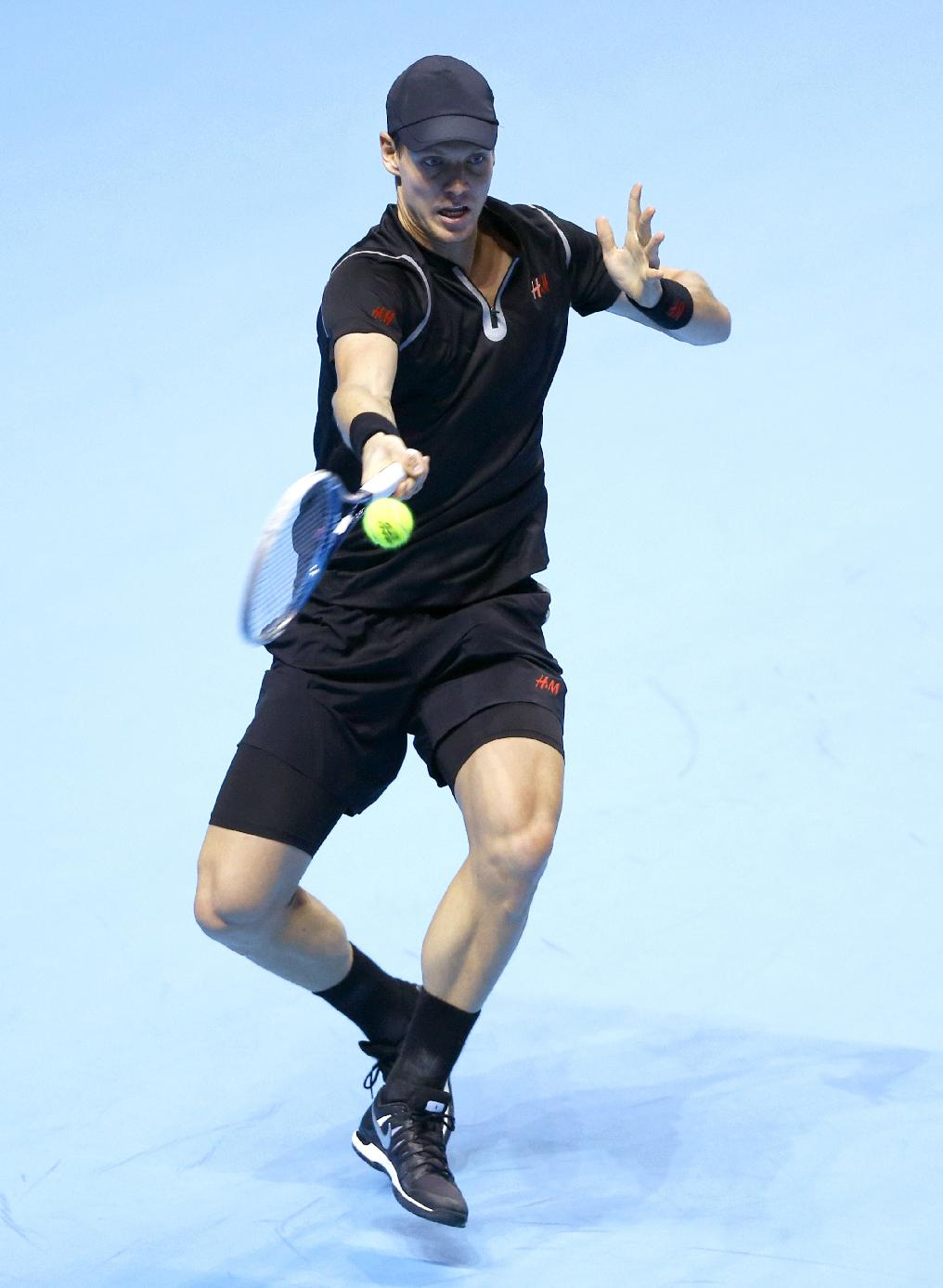 Tomas Berdych of the Czech Republic plays a return to Stanislas Wawrinka of Switzerland during their ATP World Tour Finals tennis match at the O2 Arena in London, Monday, Nov. 4, 2013