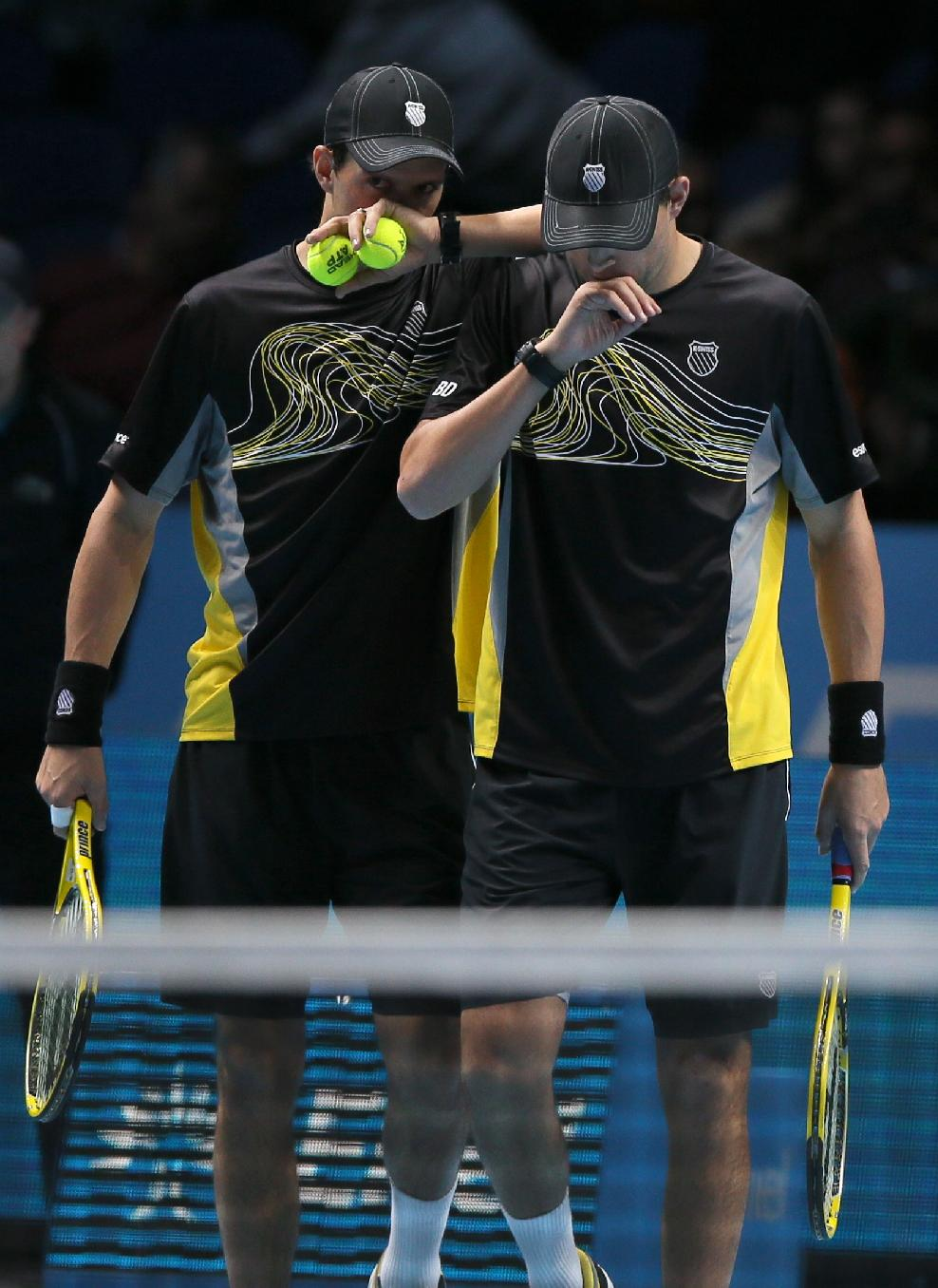 Bob Bryan of the United States, right, and Mike Bryan of the United States talk after they play a return to Mariusz Fyrstenberg of Poland and Marcin Matkowski of Poland during their ATP World Tour Finals tennis match at the O2 Arena in London, Saturday, Nov. 9, 2013