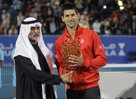 Novak Djokovic of Serbia, right, receives the winner's trophy from Sheikh Hamdan bin Mubarak Al Nahyan, UAE Minister of Higher Education and Scientific Research, after he beat David Ferrer of Spain during the final match of the Mubadala World Tennis Championship in Abu Dhabi, United Arab Emirates, Saturday, Dec. 28, 2013