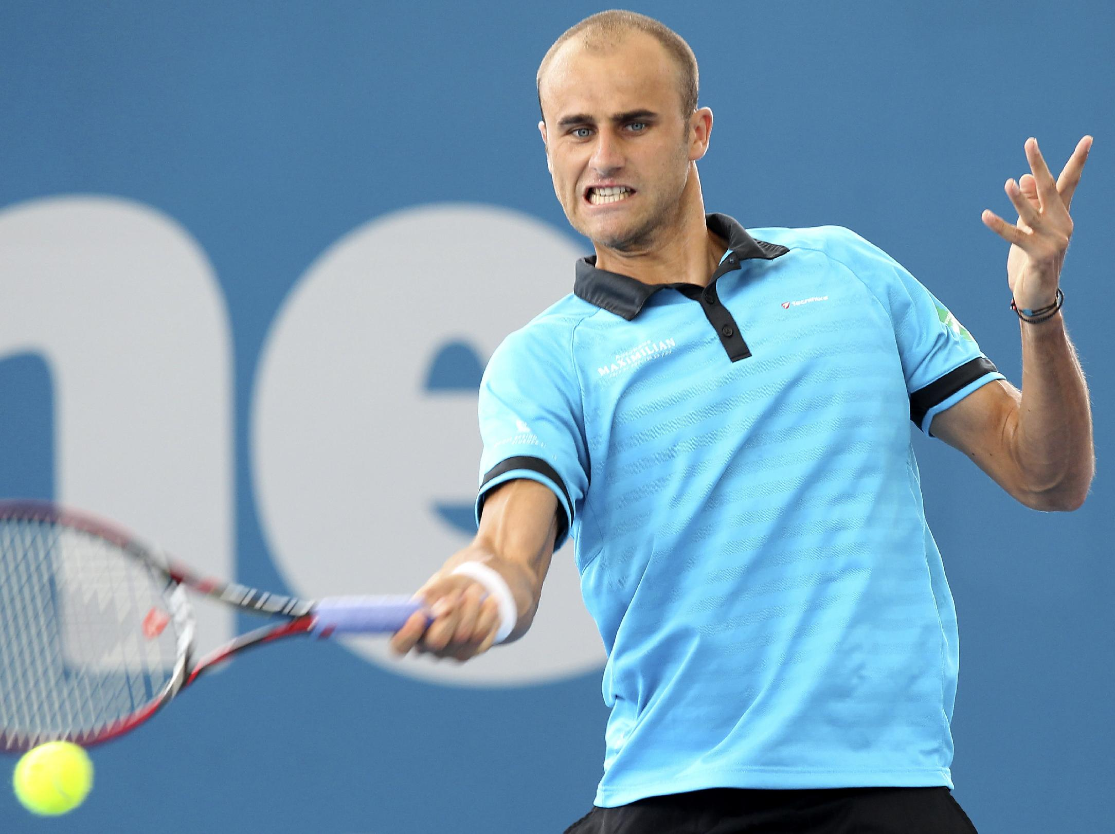 Marius Copil of Romania plays a shot in his match against Gilles Simon of France during the Brisbane International tennis tournament in Brisbane, Australia, Thursday, Jan. 2, 2014