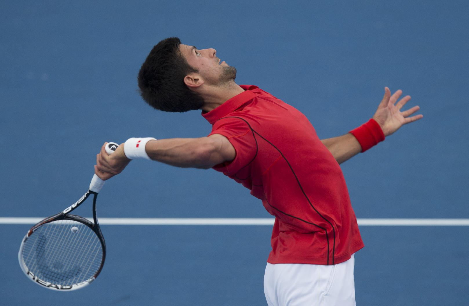 Serbia's Novak Djokovic serves to Juan Monaco of Argentina during an exhibition match at the Kooyong Classic ahead of the Australian Open tennis championship in Melbourne Australia, Thursday, Jan. 9, 2014