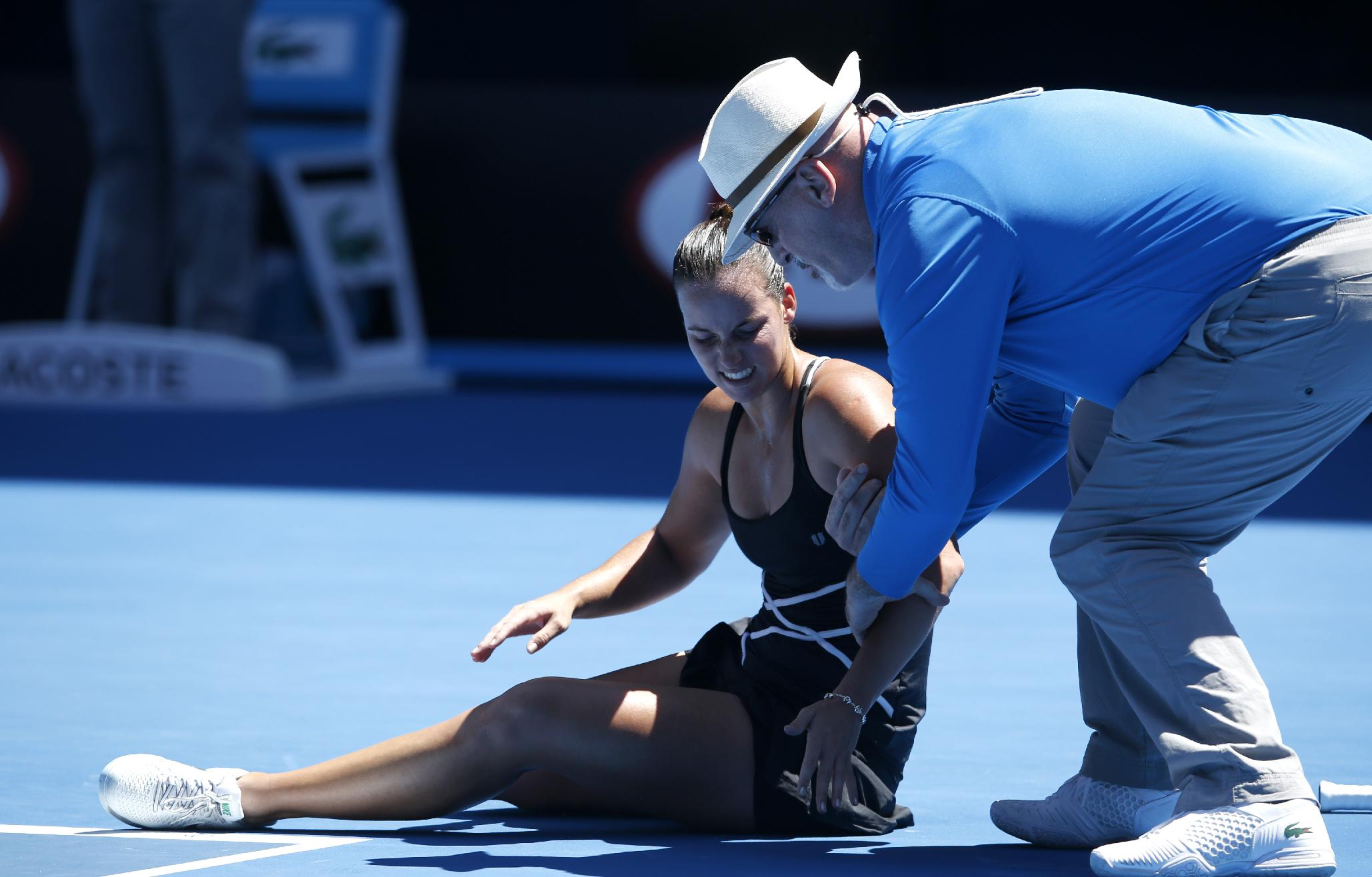Jarmila Gajdosova of Australia is assisted by  linesman after falling over during her first round match against Angelique Kerber of Germany at the Australian Open tennis championship in Melbourne, Australia, Monday, Jan. 13, 2014