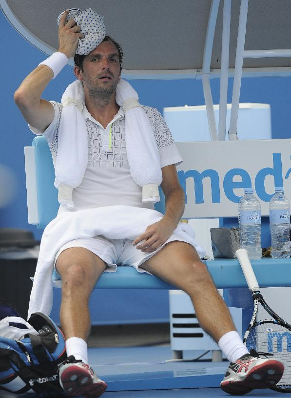 Julien Benneteau of France cools down an ice pack on his head during his second round match against Tommy Robredo of Spain at the Australian Open tennis championship in Melbourne, Australia, Wednesday, Jan. 15, 2014