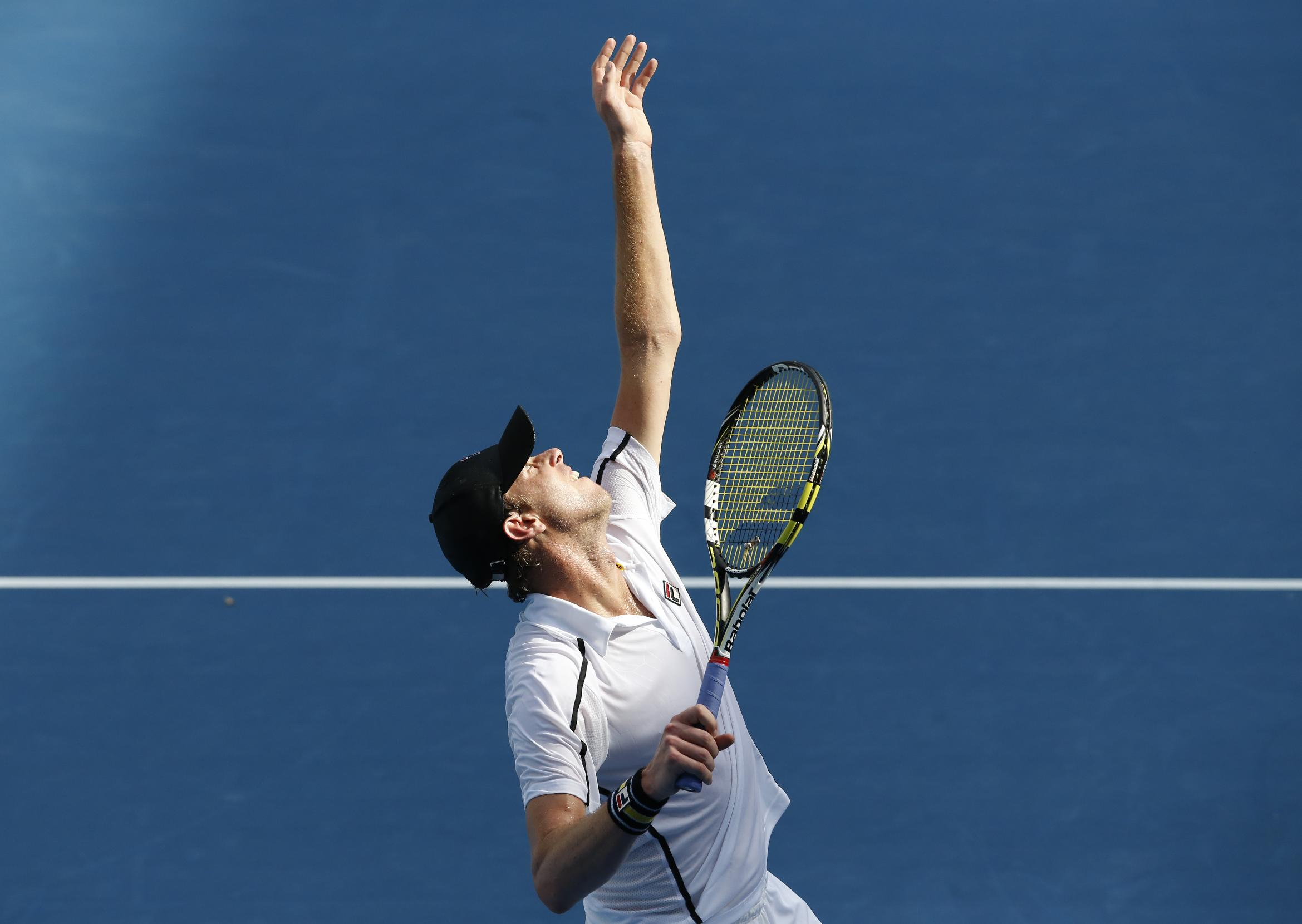 Sam Querrey of the U.S. serves to Ernests Gulbis of Latvia  during their second round match at the Australian Open tennis championship in Melbourne, Australia, Wednesday, Jan. 15, 2014