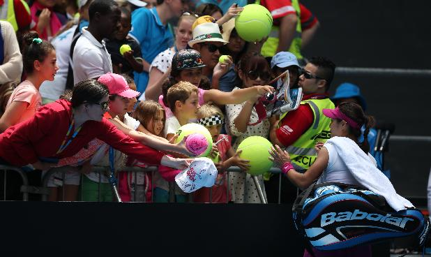 Li Na of China signs autographs for fans after her fourth round win over Ekaterina Makarova of Russia at the Australian Open tennis championship in Melbourne, Australia, Sunday, Jan. 19, 2014