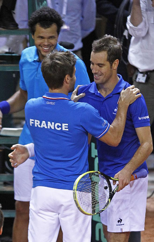 French team captain Arnaud Clement, center, congratulates French players Richard Gasquet, right, and Jo-Wilfried Tsonga, left, after they won their double match against Australian players Lleyton Hewitt and Chris Guccione in the first round of the Davis Cup between France and Australia, in La Roche sur Yon, western France, Saturday Feb. 1, 2014. France qualifies for the next round with a 3-0 score