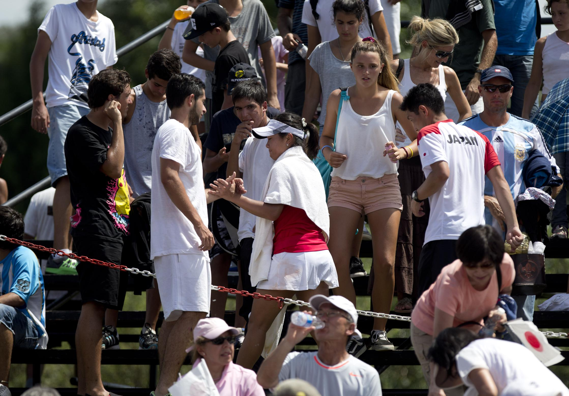 Japan's Kurumi Nara, center, shakes hands with a fan as she leaves the court after her Fed Cup World Group II tennis match in Pilar, Argentina, Saturday, Feb. 8, 2014.  Argentina's Maria Irigoyen won 6-7 (7), 6-4, 6-4