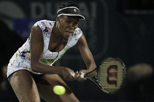 Venus Williams of the U.S. returns the ball to Elena Vesnina of Russia during the first round of Dubai Duty Free Tennis Championships in Dubai, United Arab Emirates, Monday, Feb. 17, 2014