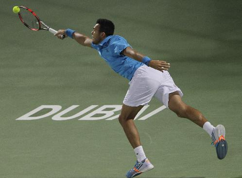 Jo Wilfried Tsonga of France returns the ball to Victor Hanescu of Romania during the second round of the Dubai Duty Free Tennis Championships in Dubai, United Arab Emirates, Tuesday, Feb. 25, 2014