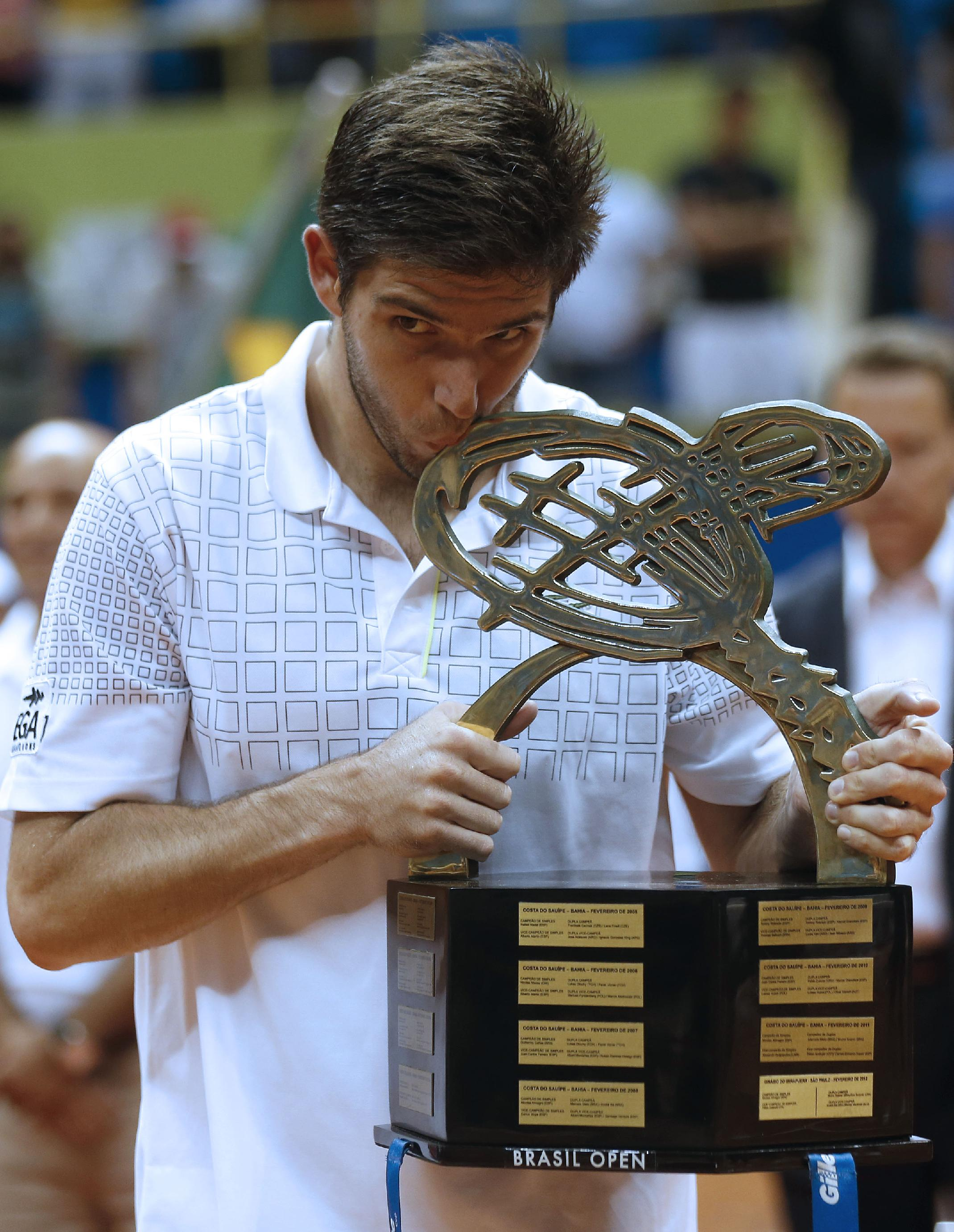 Argentina's Federico Delbonis kisses the Brazil Open ATP tennis trophy as he poses for pictures after defeating Italy's Paolo Lorenzi in Sao Paulo, Brazil, Sunday, March 2, 2014