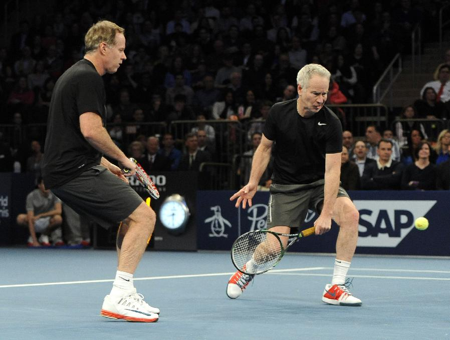 Patrick McEnroe, left, watches his brother John return a shot against Mike and Bob Bryan in the BNP Paribas Showdown Tennis Tournament on Monday, March 3, 2014, in New York. The Bryans won 8-3