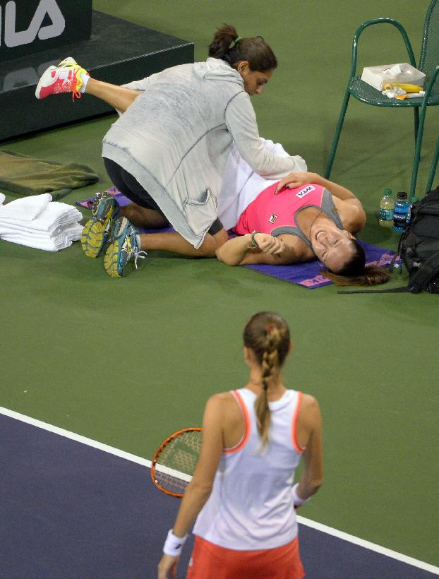 Jelena Jankovic, top, of Serbia, receives medical attention for her back as her opponent Magdalena Rybarikova, of Slovakia, looks on during their match at the BNP Paribas Open tennis tournament, Sunday, March 9, 2014, in Indian Wells, Calif