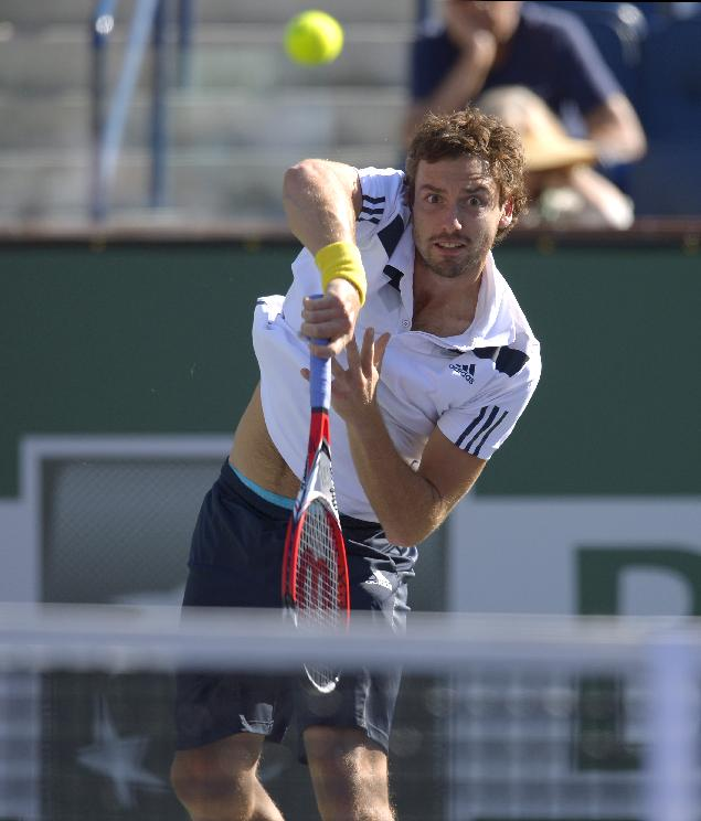Ernests Gulbis, of Latvia, hits to John Isner during their quarterfinal match at the BNP Paribas Open tennis tournament, Friday, March 14, 2014, in Indian Wells, Calif