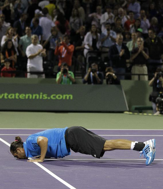 Marcos Baghdatis, of Cyprus, kisses the court surface after defeating  Santiago Giraldo, of Colombia, 1-6, 6-2, 7-5 during the Sony Open tennis tournament, Wednesday, March 19, 2014, in Key Biscayne, Fla