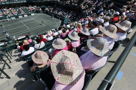 Tennis fans all wear the same style hats to protect them from the sun during the Chanelle Scheepers, of South Africa, and Venus Williams match on Billie Jean Court during the Family Circle Cup tennis tournament in Charleston, S.C., Wednesday, April 2, 2014