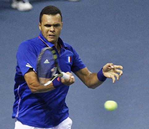 French tennis player Jo-Wifried Tsonga returns the ball to German player Peter Gojowczyk, during their single match in the quarterfinals of the Davis Cup in Nancy, eastern France, Friday April 4, 2014. France plays against Germany from Friday April 4 to Sunday April 6