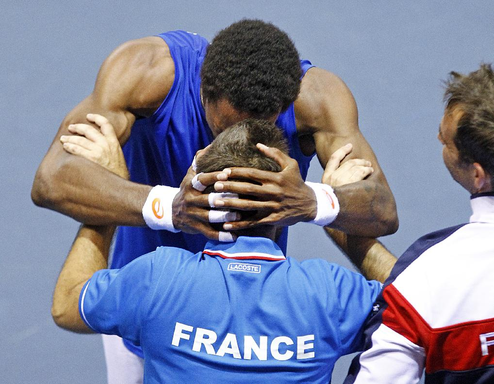 France's Gael Monfils celebrates with a French team member, after winning his singles match against German player Peter Gojowczyk, in the quarterfinals of the Davis Cup in Nancy, eastern France, Sunday April 6, 2014.  France qualifies for the semifinals with a 3-2 score