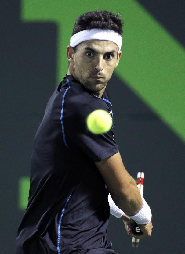 Santiago Giraldo, of Colombia, returns the ball to Marcos Baghdatis, of Cyprus, during the Sony Open tennis tournament, Wednesday, March 19, 2014, in Key Biscayne, Fla