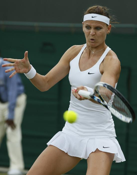Lucie Safarova of the Czech Republic plays a return to Domimika Cibulkova of Slovakia  during their women's singles match at the All England Lawn Tennis Championships in Wimbledon, London, Friday, June 27, 2014