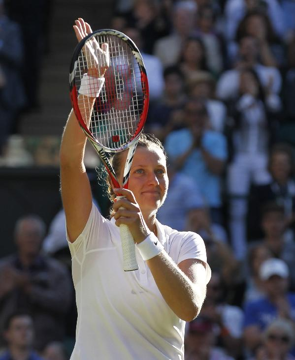 Petra Kvitova of the Czech Republic waves to the crowd after winning against Venus Williams of U.S. in their women's singles match at the All England Lawn Tennis Championships in Wimbledon, London, Friday, June 27, 2014