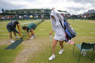 Vera Zvonareva of Russia makes her way off court sheltering under a towel as play is suspended due to rain in her women's singles match against Zarina Diyas of Kazakhstan at the All England Lawn Tennis Championships in Wimbledon, London, Saturday, June 28, 2014