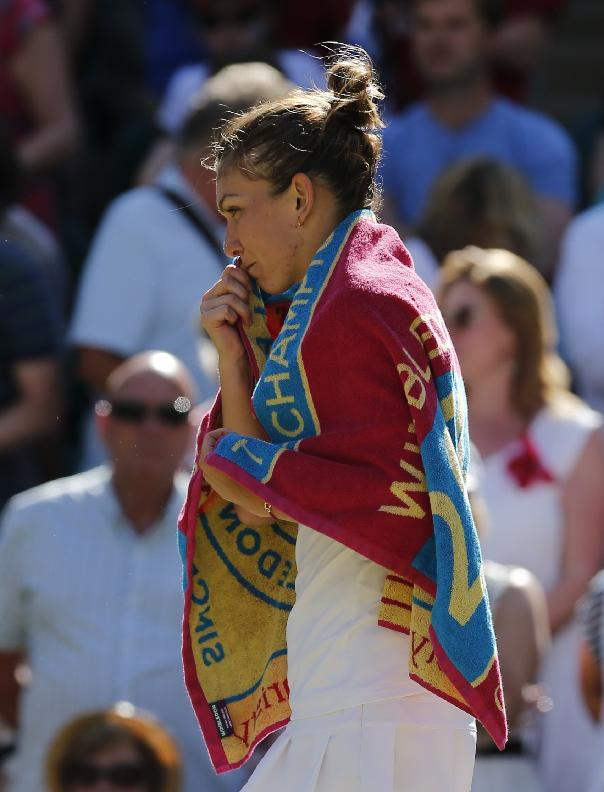 Simona Halep of Romania is covered with a towel after her women's singles semifinal match against Eugenie Bouchard of Canada  at the All England Lawn Tennis Championships in Wimbledon, London, Thursday, July 3, 2014. Halep was defeated by Bouchard