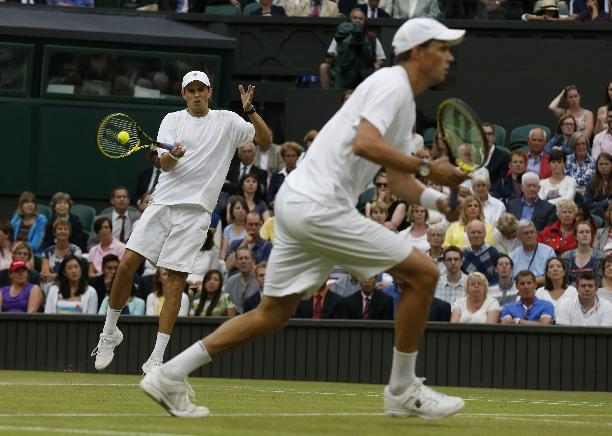 Bob Bryan, right, and Mike Bryan of the U.S play a return to Vasek Pospisil of Canada  and Jack Sock of the U.S during the men's doubles final at the All England Lawn Tennis Championships in Wimbledon, London, Saturday July 5, 2014