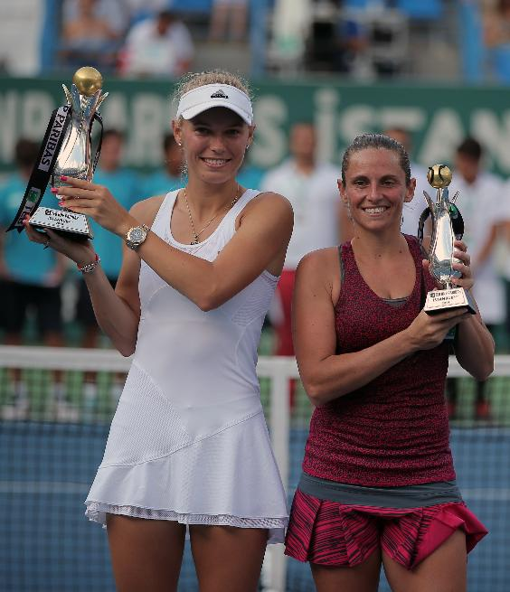 Caroline Wozniacki of Denmark, left, and Roberta Vinci of Italy hold their trophies after their tennis final match at the Istanbul Cup in Istanbul, Turkey, Sunday, July 20, 2014. Wozniacki overpowered second-seeded Vinci 6-1, 6-1 Sunday to win the Istanbul Cup final and clinch her first WTA title of the year.(AP Photo)