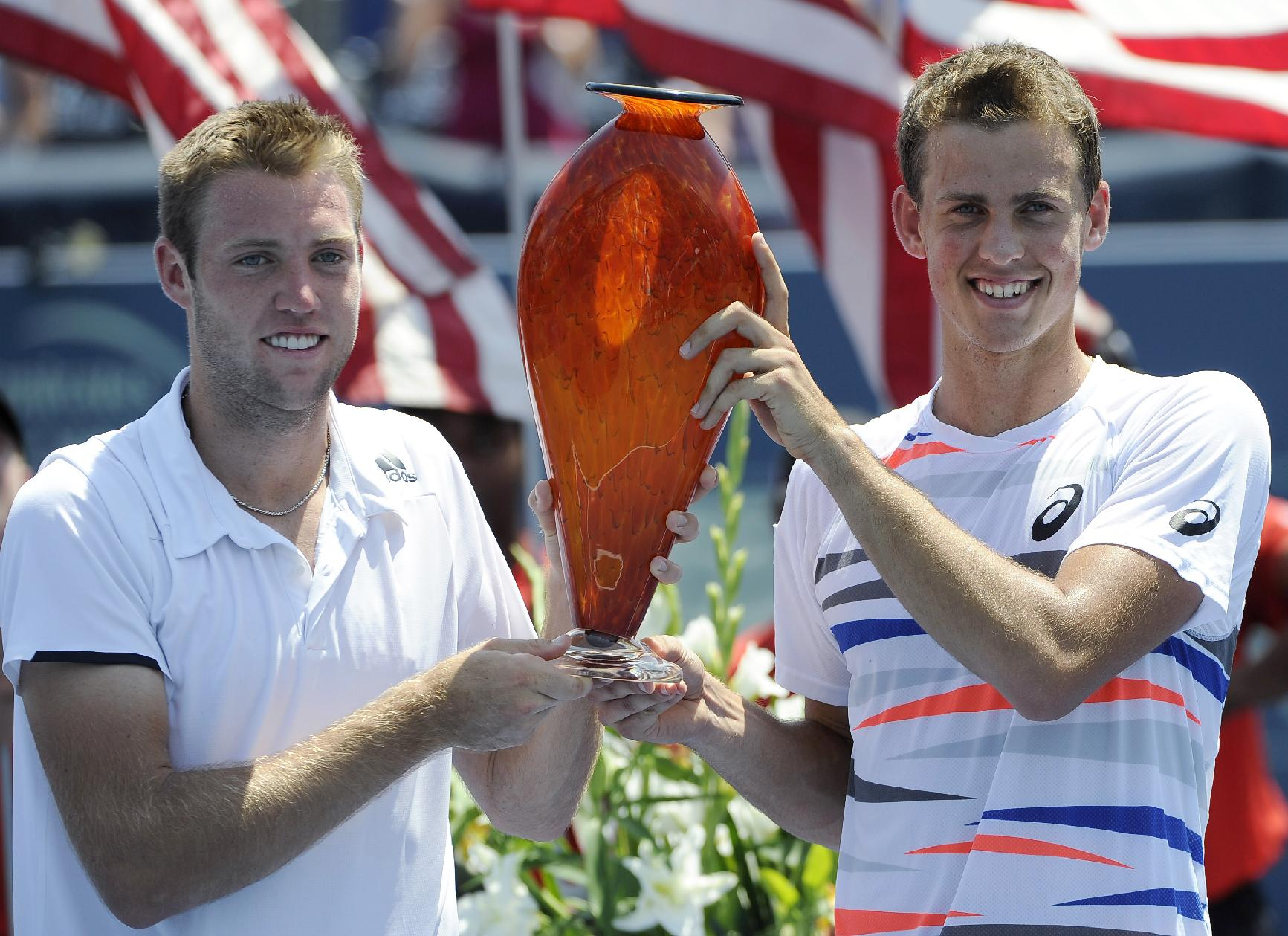 Jack Sock, left, holds the trophy with playing partner Vasek Pospisil after they defeated Steve Johnson and Sam Querry 6-3, 5-7, 10-5 to win the doubles final in the Atlanta Open tennis tournament Sunday, July 27, 2014, in Atlanta