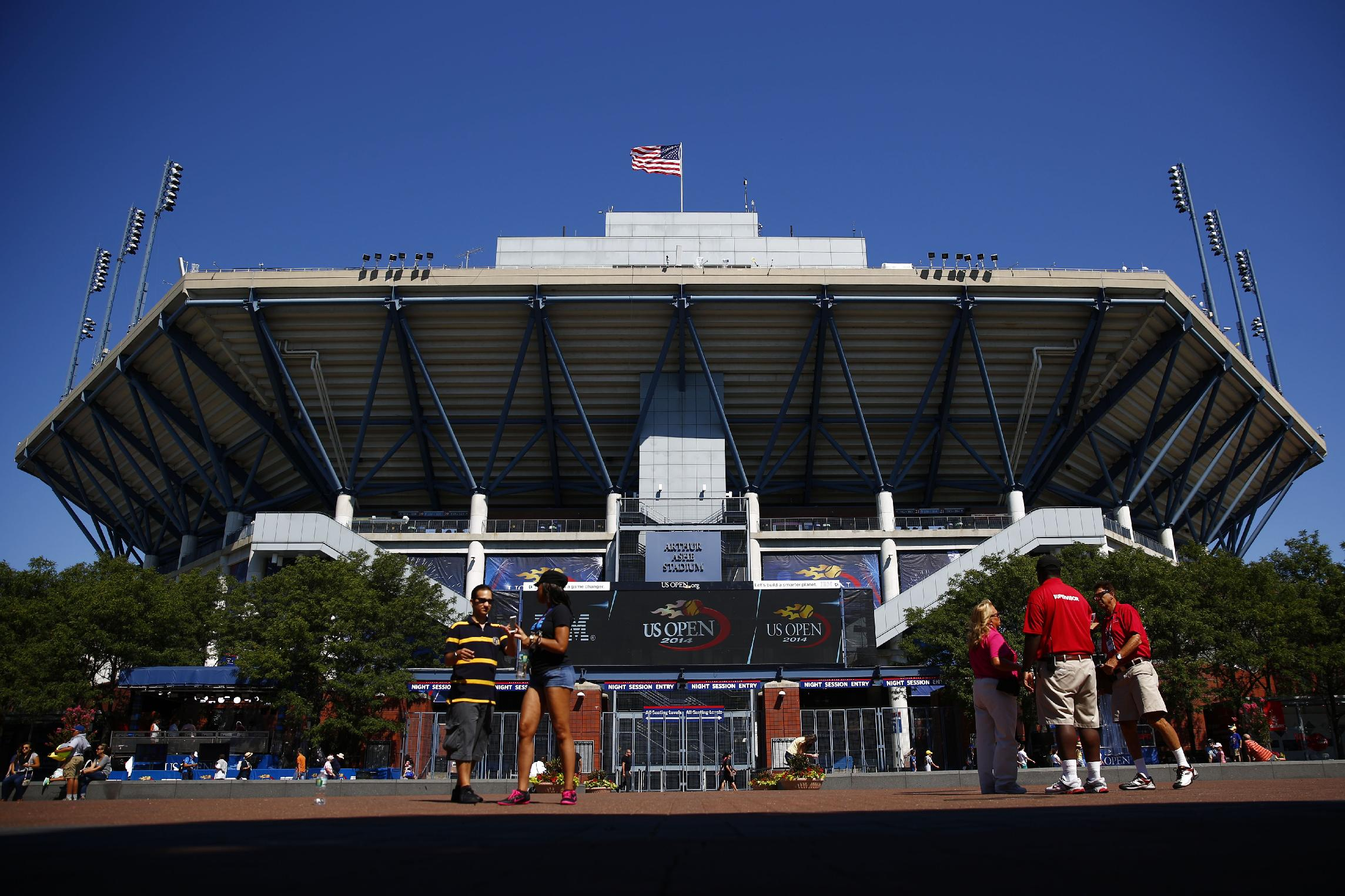 People walk past  Arthur Ashe Stadium ahead of the of the 2014 U.S. Open tennis tournament, Sunday, Aug. 24, 2014, in New York