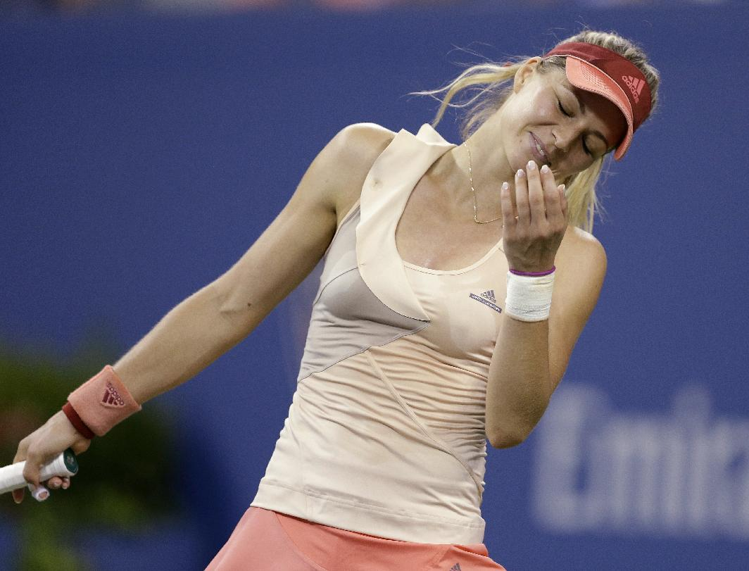 Maria Kirilenko, of Russia, reacts after missing a shot against Maria Sharapova, of Russia, during the opening round of the U.S. Open tennis tournament Monday, Aug. 25, 2014, in New York