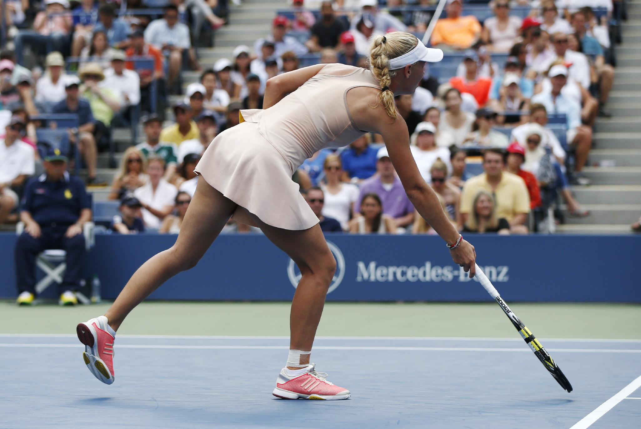 Caroline Wozniacki, of Denmark, points out a spot near the service line during a fourth round match against Maria Sharapova, of Russia, during the 2014 U.S. Open tennis tournament, Sunday, Aug. 31, 2014, in New York