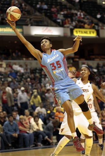 In this Oct. 2, 2012 file photo, Atlanta Dream guard Angel McCoughtry (35) goes to the basket in front of Indiana Fever forward Erlana Larkins during the first half of a WNBA basketball first-round playoff game in Indianapolis. After advancing to the 2010 and 2011 WNBA finals, the Atlanta Dream endured a tumultuous 2012 season, but star Angel McCoughtry and three other starters are returning for the 2013 season