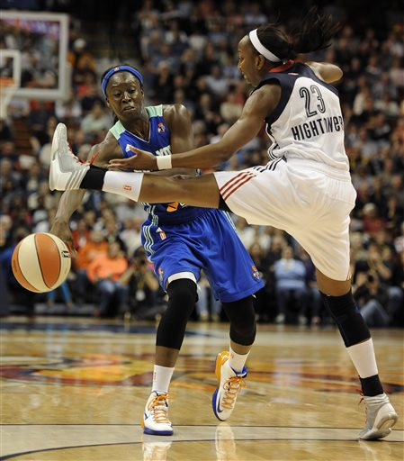 New York Liberty's Essence Carson, left, passes the ball past Connecticut Sun's Allison Hightower, right, during the first half of a WNBA basketball game in Uncasville, Conn., Saturday, May 25, 2013