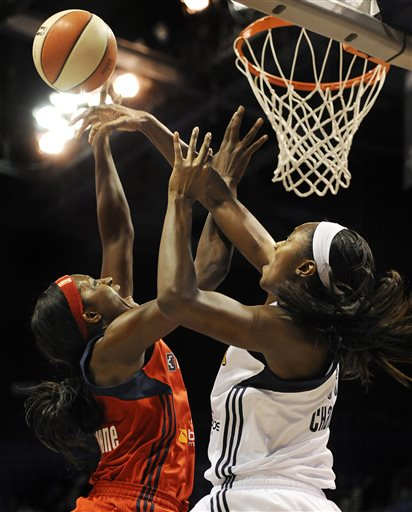 Connecticut's Tina Charles, right, blocks a shot-attempt by Washington Mystics' Crystal Langhorne, left, during the first half of a WNBA basketball game in Uncasville, Conn., Friday, June 7, 2013
