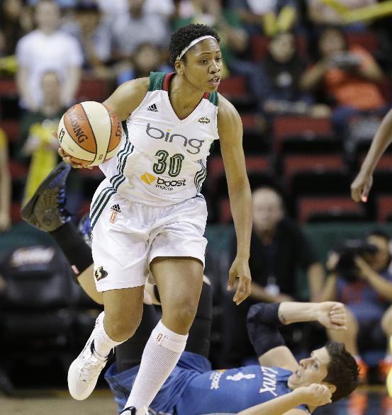 Seattle Storm's Tanisha Wright heads downcourt as Minnesota Lynx's Janel McCarville tumbles behind her in the first half of a WNBA basketball game Tuesday, Sept. 10, 2013, in Seattle