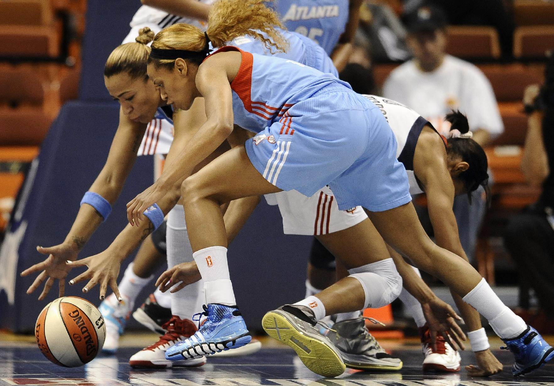 Atlanta Dream's Erika de Souza, left, and Jasmine Thomas, center, chase a loose ball as Connecticut Sun's Iziane Castro Marques right, falls to the court during the first half of a WNBA basketball game in Uncasville, Conn., Wednesday, Sept. 11, 2013