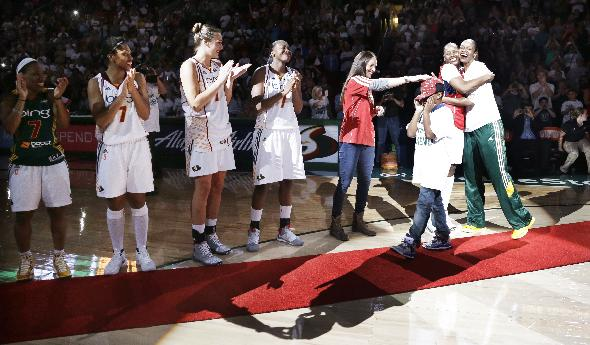 Seattle Storm's Tina Thompson, right, is greeted by a line of teammates as she walk with her son, Dyllan, 8, to a ceremony honoring her after her final regular season WNBA basketball game Saturday, Sept. 14, 2013, in Seattle. The Storm won 85-73