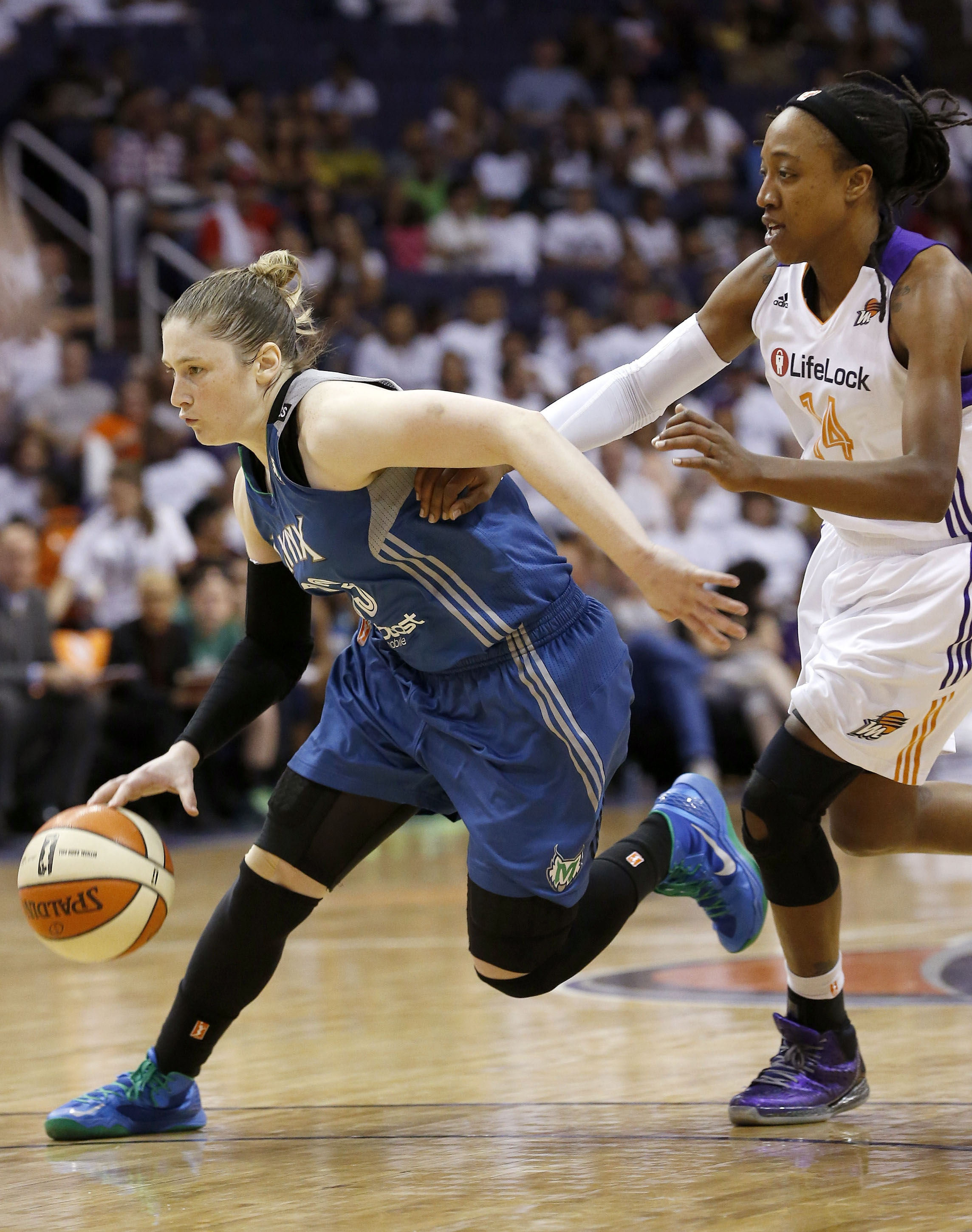 Minnesota Lynx's Lindsay Whalen, left, dribbles past Phoenix Mercury's Alexis Hornbuckle (14) during the second half in a WNBA Western Conference Finals basketball game on Sunday, Sept. 29, 2013, in Phoenix. The Lynx defeated the Mercury 72-65 and won the Western Conference Finals 2-0, earning a trip to the WNBA Finals to face the Atlanta Dream