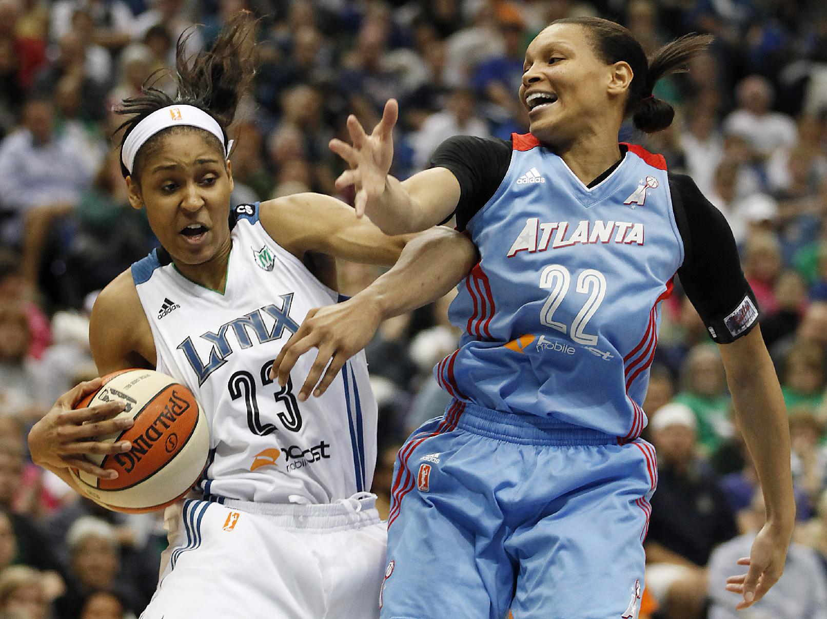 Minnesota Lynx forward Maya Moore (23) protects a rebound ball against Atlanta Dream guard Armintie Herrington (22) during the first half of Game 2 of the WNBA basketball finals, Tuesday, Oct. 8, 2013, in Minneapolis