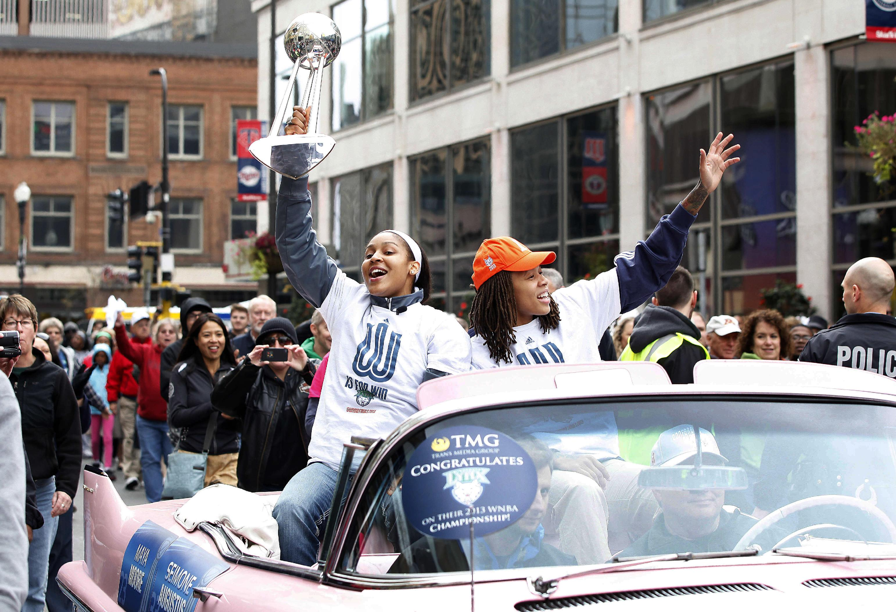 Minnesota Lynx forward Maya Moore, left, and guard Seimone Augustus, right, celebrate during the parade for their  WNBA basketball championship title, Monday, Oct. 14, 2013, in Minneapolis