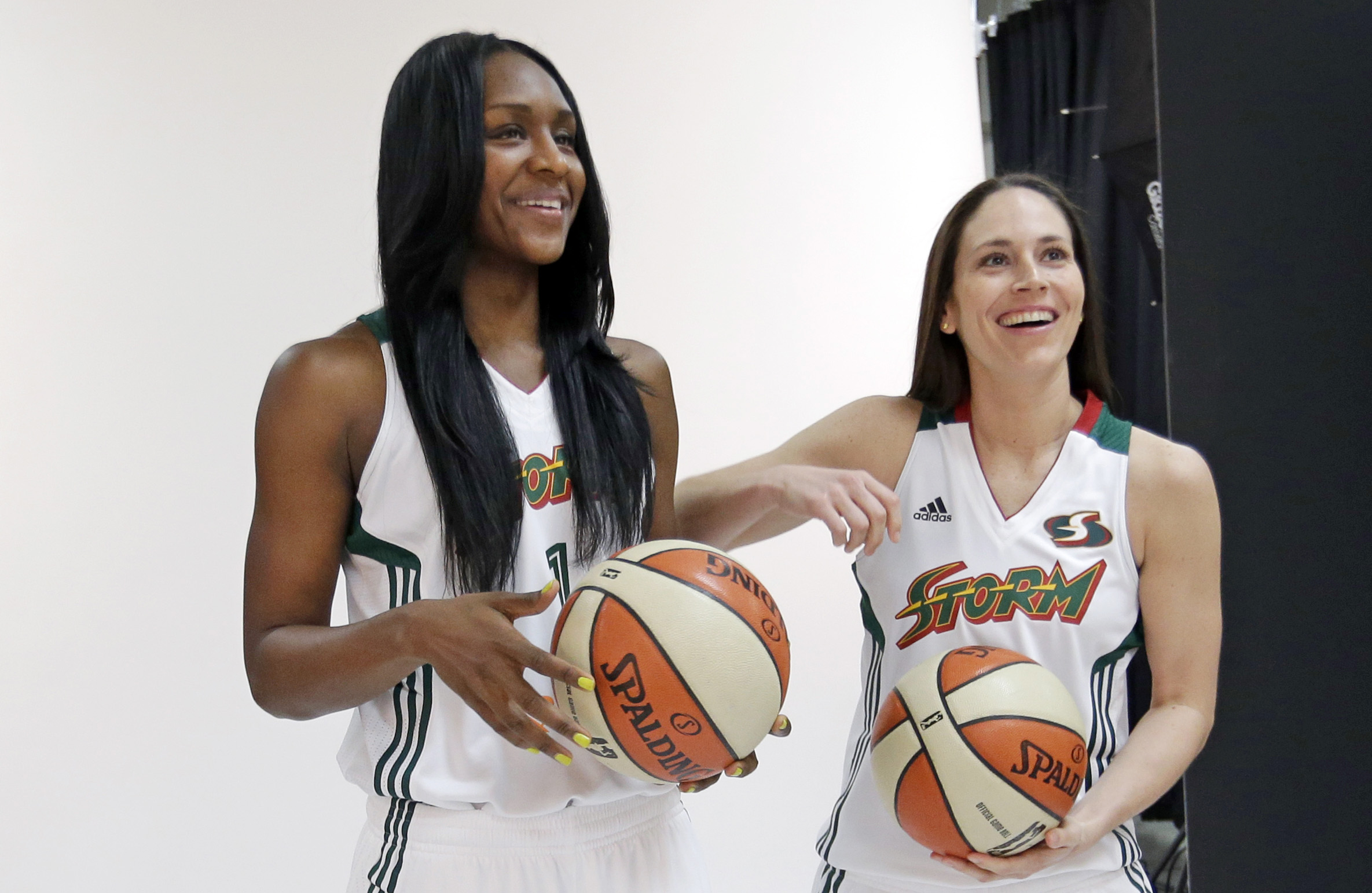 Seattle Storm's Crystal Langhorne, left, and Sue Bird begin a photo session at the team's annual media day Wednesday, May 7, 2014, in Seattle. The team opens against the Los Angeles Sparks on May 16 in Seattle
